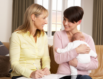 Midwife providing a home visit for a new mother and baby