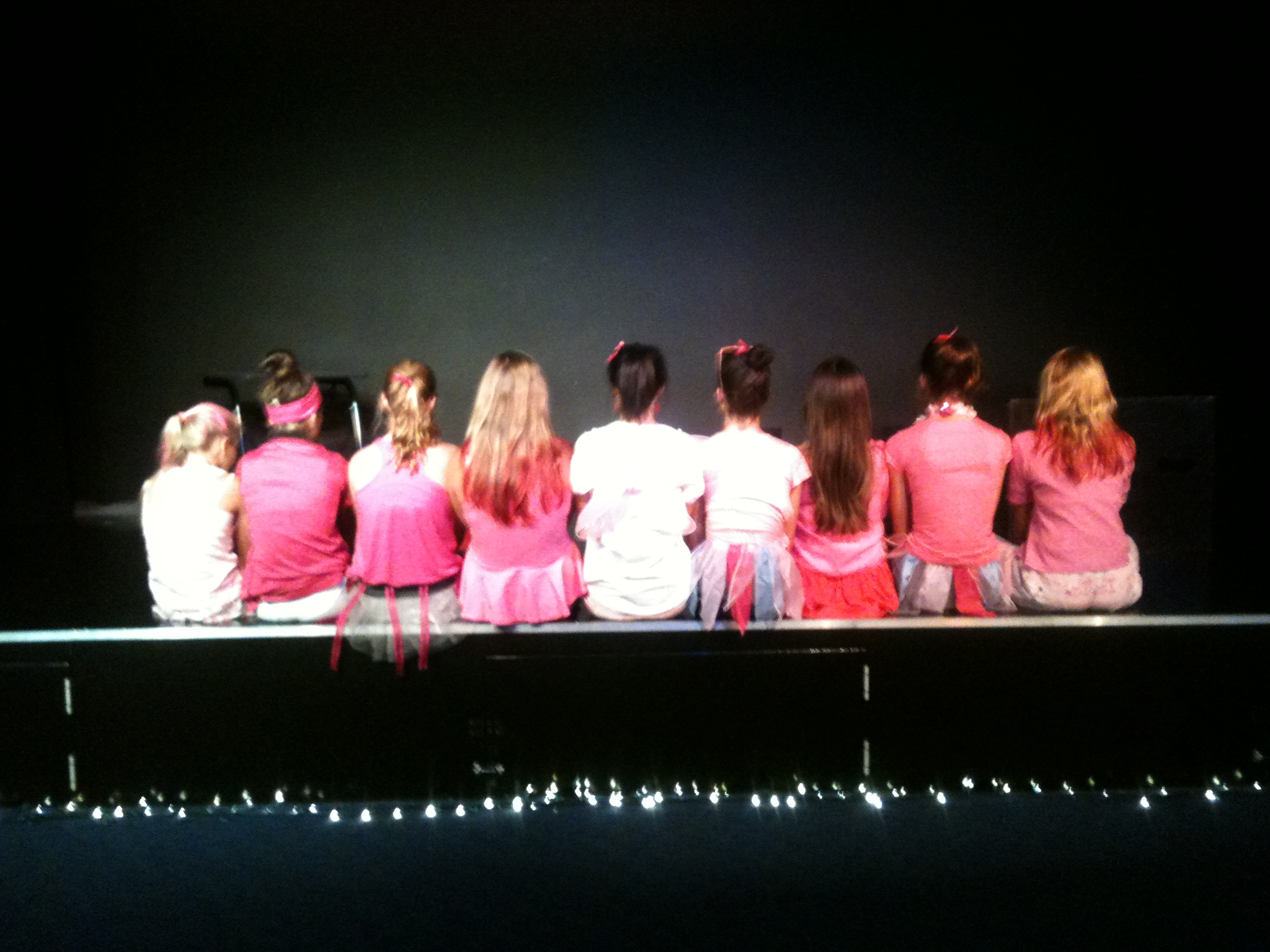 my students and I sitting on the stage. just the girls. I wanted the boys in the photo too but they were being too silly!